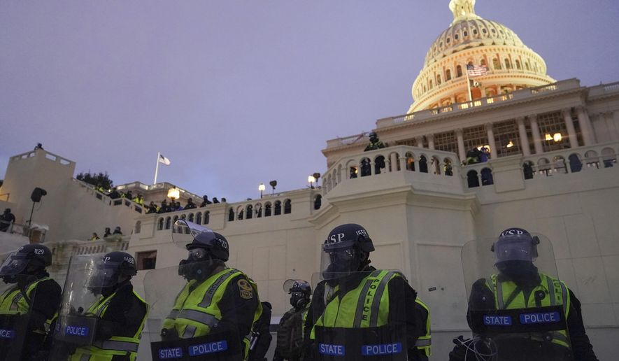 In this Wednesday, Jan. 6, 2021, file photo, police form a line to guard the U.S. Capitol after violent rioters stormed the building, in Washington. (AP Photo/John Minchillo)