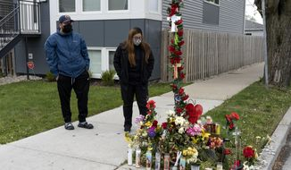 Two people leave objects at a memorial for Anthony Alvarez, Wednesday, April 28, 2021, in the Portage Park neighborhood of Chicago, near the place where a Chicago police officer shot and killed the 22-year-old during a foot chase in the early morning hours of March 31. (Erin Hooley/Chicago Tribune via AP)