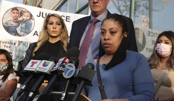 Veronica Alvarez, foreground, the mother of 22-year-old Anthony Alvarez, reads a statement to the media on Tuesday, April 27, 2021, after watching video of her son's fatal shooting. Her attorney Todd Pugh stands behind her. (Terrence Antonio James/Chicago Tribune via AP)