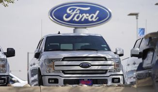 FILE - In this Sunday, Oct. 11, 2020, file photo, a row of 2020 sports-utility vehicles pickup trucks sits at a Ford dealership, in Denver. Ford Motor Co. says it made $3.26 billion in the first quarter, helped by rising vehicle prices and in spite of production cuts due to a global shortage of computer chips. The earnings reversed a nearly $2 billion net loss from a year ago, when Ford burned through cash at the start of the coronavirus pandemic. (AP Photo/David Zalubowski, File)