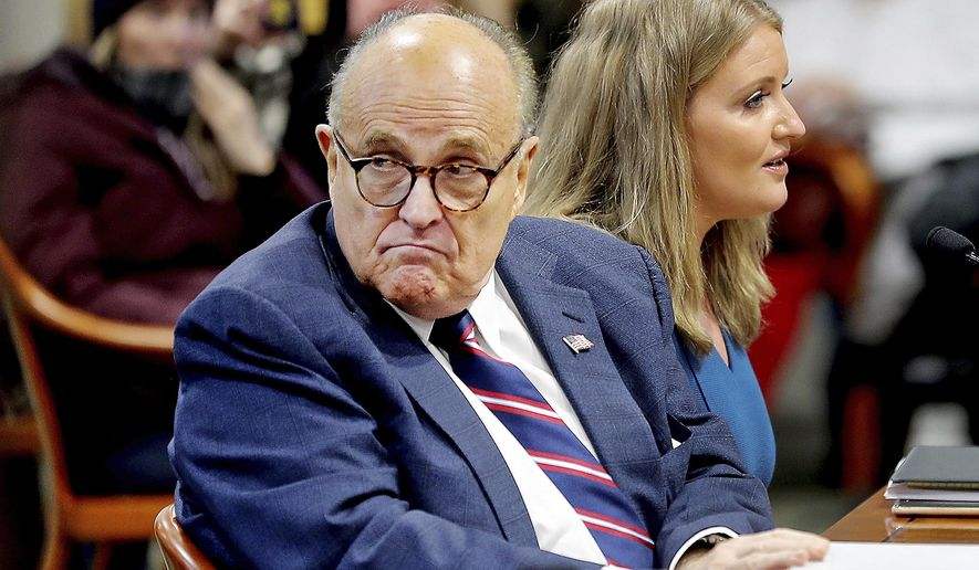 In this Dec. 2, 2020, file photo, Rudy Giuliani, then-President Donald Trump's personal attorney, scans the room during a Michigan House Oversight Committee hearing on suspicion of voter fraud within the state at the House Office Building in Lansing, Mich. Federal agents raided Giuliani's Manhattan home and office on Wednesday, April 28, 2021, seizing computers and cellphones in a major escalation of the Justice Department's investigation into the business dealings of former President Donald Trump's personal lawyer. (Mike Mulholland/The Grand Rapids Press via AP)