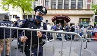 New York City police officers set up barricades to contain members of the media outside the building where Rudy Giuliani lives, Wednesday, April 28, 2021, in New York. A law enforcement official tells The Associated Press that federal investigators have executed search warrants at Rudy Giuliani's Manhattan residence and office. The former New York City mayor has been under investigation for several years over his business dealings in Ukraine. Details of the reasons for Wednesday's searches were not immediately available. (AP Photo/Mary Altaffer)