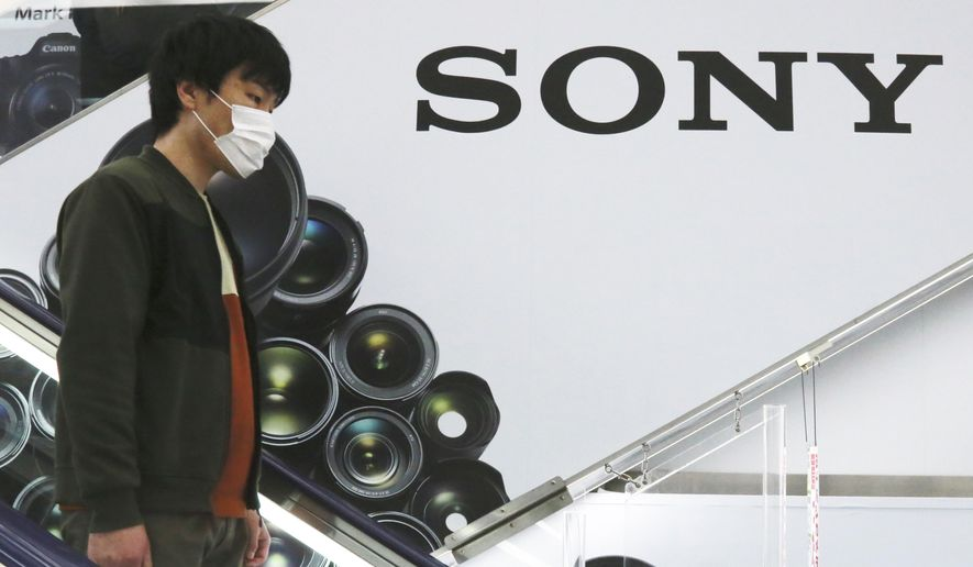 A man stands by the logo of Sony at an electronics retail chain store in Tokyo, Wednesday, April 28, 2021. Sony's January-March profit zoomed eight-fold to 107 billion yen ($982 million) as people stuck at home during the coronavirus pandemic turned to the Japanese electronics and entertainment company's video games and other visual content. (AP Photo/Koji Sasahara)