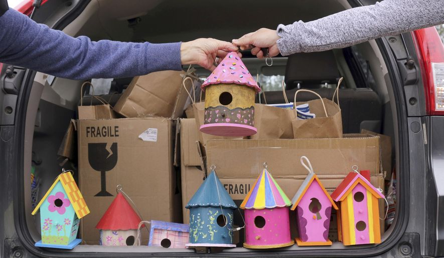 Lauren Farrar, of West Lebanon, N.H., right, hands off a birdhouse to West Lebanon Birdhouse Project co-organizer Kim Wenger Hall, also of West Lebanon, as a group gathers to hang the painted birdhouses in the village on Sunday, April 25, 2021, in Lebanon, N.H. More than 100 people signed up for the project. (Geoff Hansen/The Valley News via AP)