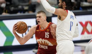 Denver Nuggets center Nikola Jokic, (15) drives to the rim as New Orleans Pelicans center Steven Adams defends in the first half of an NBA basketball game Wednesday, April 28, 2021, in Denver. (AP Photo/David Zalubowski)