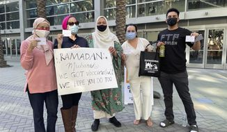 """A group of Muslims display their vaccination cards and a sign reading """"Ramadan Mubarak: We got vaccinated. We hope you do too,"""" on Sunday, April 11, 2021, at the Anaheim Convention Center in Anaheim, California. Rida Hamida, second from left, is the executive director of Latino & Muslim Unity.  (Courtesy of Latino & Muslim Unity via AP)"""