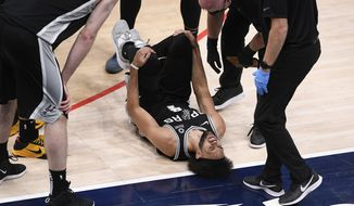 San Antonio Spurs guard Derrick White (4) reacts after he was injured during the second half of an NBA basketball game against the Washington Wizards, Monday, April 26, 2021, in Washington. (AP Photo/Nick Wass)