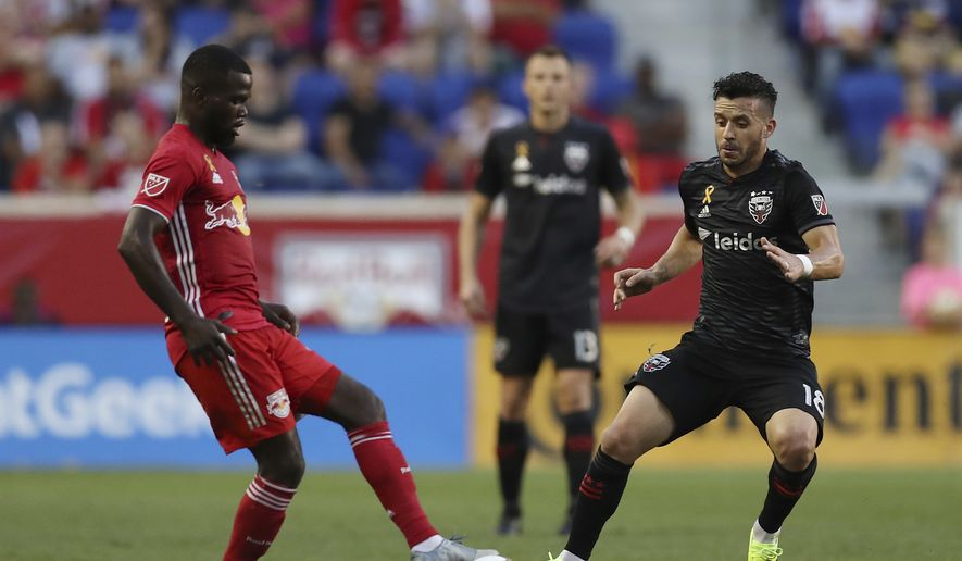 New York Red Bulls defender Kemar Lawrence (92) and D.C. United midfielder Felipe Martins (18) both attempt to control the ball during the first half of an MLS soccer match, Sunday, Sept. 29, 2019, in Harrison, N.J. The match ended in a 0-0 draw. (AP Photo/Steve Luciano) **FILE**