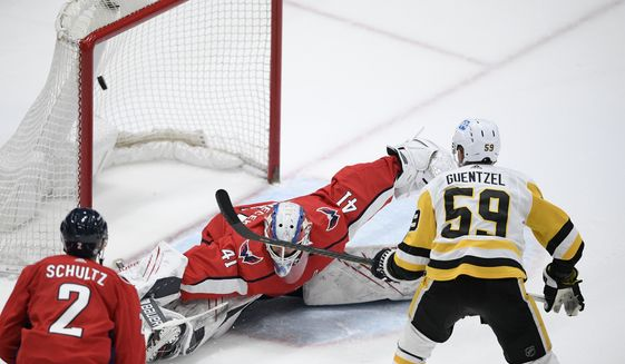 Pittsburgh Penguins left wing Jake Guentzel (59) scores against Washington Capitals goaltender Vitek Vanecek (41) in overtime of an NHL hockey game Thursday, April 29, 2021, in Washington. Also seen is Capitals defenseman Justin Schultz (2). (AP Photo/Nick Wass)