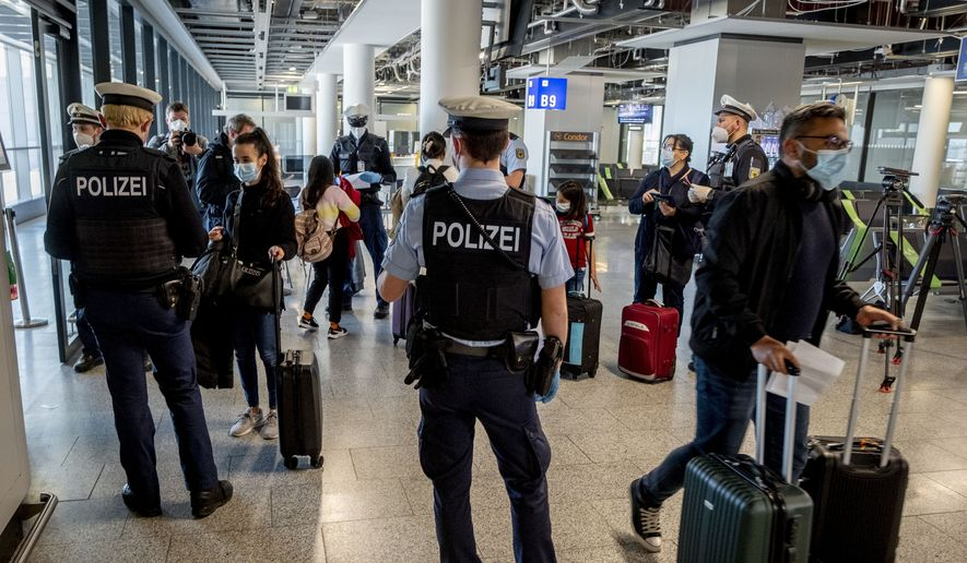 In this March 30, 2021, file photo, German federal police officers check passengers arriving from Palma de Mallorca for a negative coronavirus test as they arrive at the airport in Frankfurt, Germany. The European Commission proposed Thursday, April 29, 2021, issuing Digital Green Certificates to EU residents to facilitate travel across the 27-nation bloc by the summer 2021, as long as they have been vaccinated, tested negative for COVID-19 or recovered from the disease. (AP Photo/Michael Probst, File)