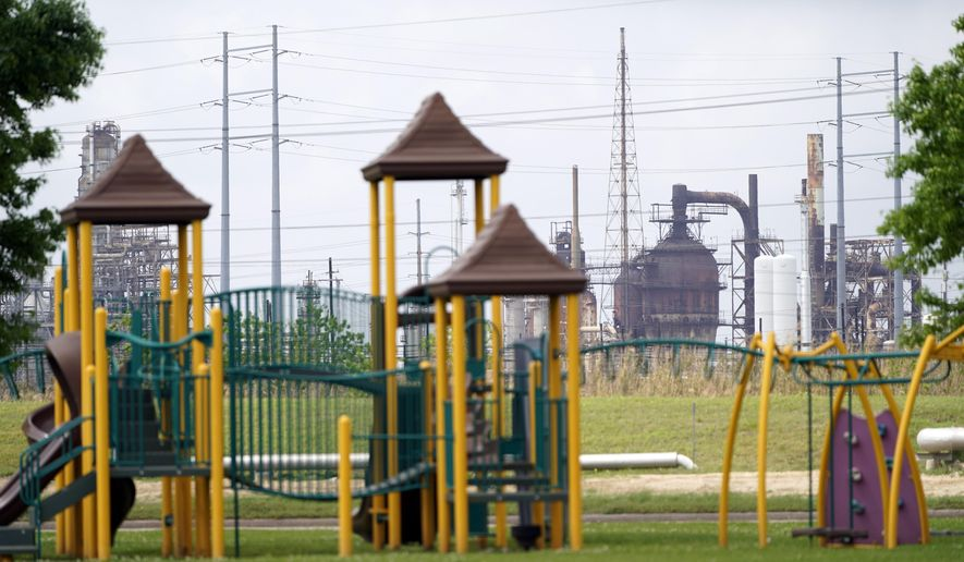 FILE - In this Monday, March 23, 2020 file photo, a playground outside the Prince Hall Village Apartments sits empty near one of the petrochemical facilities in Port Arthur, Texas. According to a study published Wednesday, April 28, 2021 in the journalScience Advances, across America, people of color are disproportionately exposed to air pollution from industry, vehicles, construction and many other sources. (AP Photo/David J. Phillip)