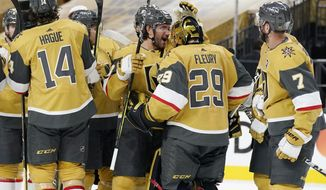 Vegas Golden Knights defenseman Alec Martinez, center left, celebrates with goaltender Marc-Andre Fleury (29) after defeating the Colorado Avalanche in an NHL hockey game Wednesday, April 28, 2021, in Las Vegas. (AP Photo/John Locher)