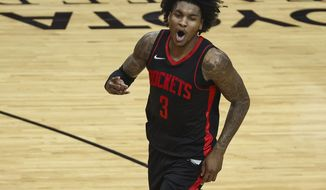 Houston Rockets guard Kevin Porter Jr. (3) reacts after making a basket during the fourth quarter of an NBA basketball game against the Milwaukee Bucks Thursday, April 29, 2021, in Houston. (Troy Taormina/Pool Photo via AP)