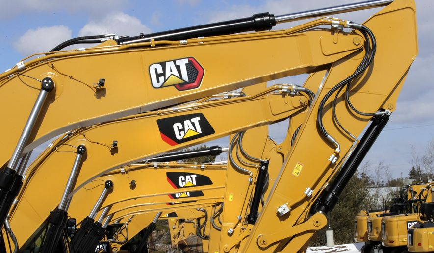 """Excavator booms, adorned with the Caterpillar Inc. """"CAT"""" logo are displayed at the Milton CAT dealership in Londonderry, N.H., Thursday, Feb. 20, 2020. Caterpillar's sales rose in the first quarter as market conditions for the machinery company begin to improve and dealers increase their inventory levels. (AP Photo/Charles Krupa)"""