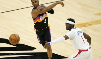 Phoenix Suns guard Chris Paul (3) passes as Los Angeles Clippers guard Reggie Jackson (1) defends during the first half of an NBA basketball game, Wednesday, April 28, 2021, in Phoenix. (AP Photo/Matt York)