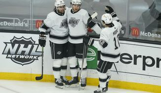 Los Angeles Kings center Gabriel Vilardi (13) celebrates with right wing Alex Iafallo (19) and center Trevor Moore (12) after Vilardi scored a goal during the second period of an NHL hockey game against the Anaheim Ducks Wednesday, April 28, 2021, in Los Angeles. (AP Photo/Ashley Landis)