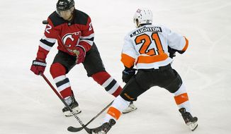 The puck flies in front of New Jersey Devils defenseman Ryan Murray (22) with Philadelphia Flyers center Scott Laughton (21) watching during the second period of an NHL hockey game Thursday, April 29, 2021, in Newark, N.J. (AP Photo/Kathy Willens)