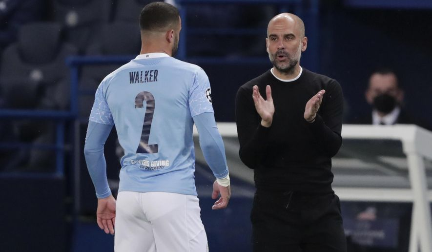 Manchester City's head coach Pep Guardiola, right, talks to Manchester City's Kyle Walker during the Champions League semifinal first leg soccer match between Paris Saint Germain and Manchester City at the Parc des Princes stadium, in Paris, France , Wednesday, April 28, 2021. (AP Photo/Thibault Camus)