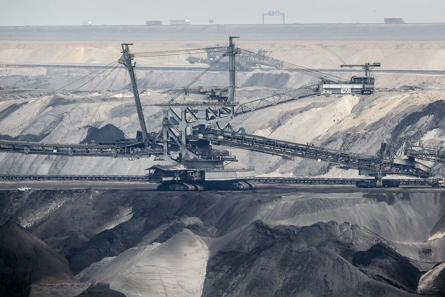 Giant bucket-wheel excavators extract coal at the controversial Garzweiler surface coal mine near Jackerath, west Germany, Thursday, April 29, 2021. Germany's top court ruled Thursday that the country's government has to set clear goals for reducing greenhouse gas emissions after 2030, arguing that current legislation doesn't go far enough in ensuring that climate change is limited to acceptable levels. (AP Photo/Martin Meissner)