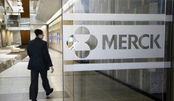 In this Dec. 18, 2014, file photo, a person walks through a Merck company building in Kenilworth, N.J. (AP Photo/Mel Evans, File) **FILE**