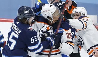 Winnipeg Jets' Mark Scheifele (55) and Edmonton Oilers' Darnell Nurse (25) mix it up during the second period of an NHL hockey game, Wednesday, April 28, 2021 in Winnipeg, Manitoba. (John Woods/The Canadian Press via AP)
