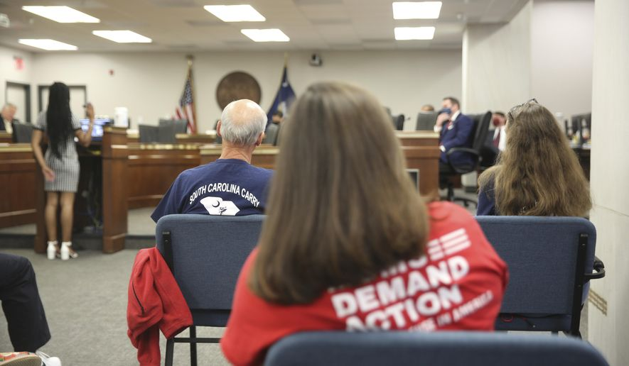 People listen to a Senate subcommittee hearing about a bill that would allow people who already have concealed weapons permits to carry their guns in the open on Tuesday, April 27, 2021, in Columbia, S.C. The bill doesn't appear to have time to pass this session. (AP Photo/Jeffrey Collins)
