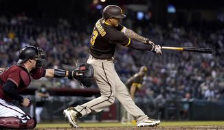 San Diego Padres' Manny Machado swings on a three-run triple next to Arizona Diamondbacks catcher Carson Kelly during the fifth inning of a baseball game Wednesday, April 28, 2021, in Phoenix. (AP Photo/Ross D. Franklin)
