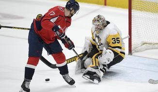Washington Capitals left wing Michael Raffl (17) and Pittsburgh Penguins goaltender Tristan Jarry (35) vie for the puck during the second period of an NHL hockey game Thursday, April 29, 2021, in Washington. (AP Photo/Nick Wass)