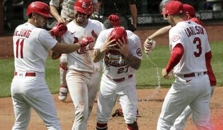 St. Louis Cardinals' Tyler O'Neill (27) celebrates with teammates Paul DeJong (11), Dylan Carlson (3), and Edmundo Sosa (63) after scoring a run on a wild pitch by Philadelphia Phillies' David Hale in the tenth inning of a baseball game, Thursday, April 29, 2021 in St. Louis. The Cardinals beat the Phillies 4-3 in 10 innings.(AP Photo/Tom Gannam)
