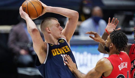 Denver Nuggets center Nikola Jokic, left, pulls in a rebound as Toronto Raptors center Khem Birch defends in the first half of an NBA basketball game Thursday, April 29, 2021, in Denver. (AP Photo/David Zalubowski)