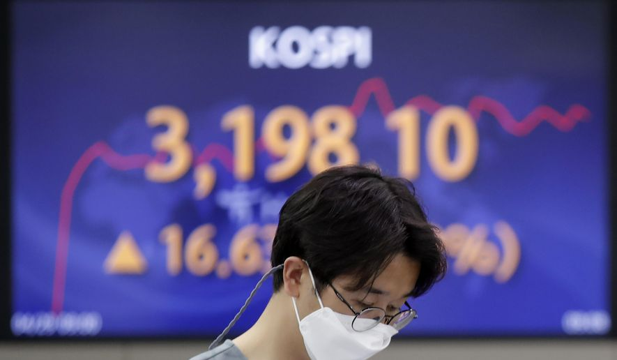 A currency trader walks near the screen showing the Korea Composite Stock Price Index (KOSPI) at the foreign exchange dealing room in Seoul, South Korea, Thursday, April 29, 2021. Asian shares rose Thursday and U.S. futures also were higher after President Joe Biden delivered a speech to Congress that outlined ambitious plans for jobs creating spending on early education, child care and other public services. (AP Photo/Lee Jin-man)