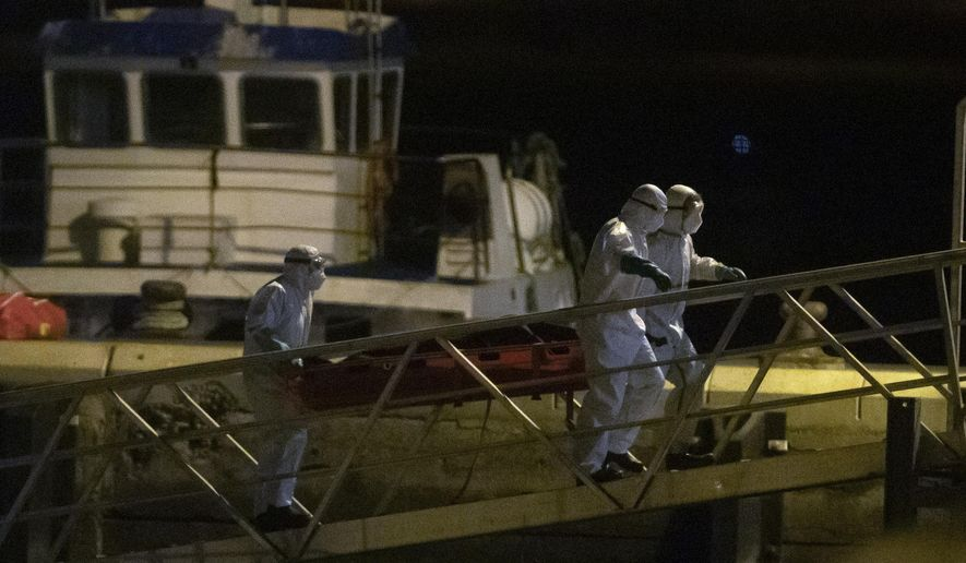Emergency services carry dead bodies of migrants after being recovered from a wooden boat at the port of Los Cristianos in the south of Tenerife, in the Canary Island, Spain, Wednesday, April 28, 2021. Spanish authorities have brought to shore the bodies of 24 migrants from sub-Saharan Africa, among them two minors. The migrant boat was spotted on Monday by a Spanish military plane 265 nautical miles from the island of El Hierro, three survivors were airlifted, the others are believed to have died from thirst and hunger during the perilous migratory journey from the West coast of Africa to the Canary Islands. (AP Photo/Andres Gutierrez)