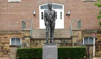 A statue of J. William Fulbright stands, Wednesday, July 1, 2020, near the west entrance of Old Main on the University of Arkansas campus in Fayetteville, Ark. A committee, comprised of students, faculty and staff members, and alumni, at the university has recommended to remove the statue of Fulbright, a former Senator who once voted against the interests of Black students and supported values antithetical to the university. (Andy Shupe/The Northwest Arkansas Democrat-Gazette via AP)