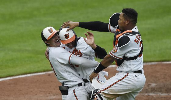 Baltimore Orioles' Austin Hayes, left, hugs Ramon Urias, center, as Pedro Severino taps his head after he scores the winning run against the New York Yankees in the 10th inning of a baseball game, Thursday, April 29, 2021, in Baltimore. The Orioles won 4-3.(AP Photo/Gail Burton)