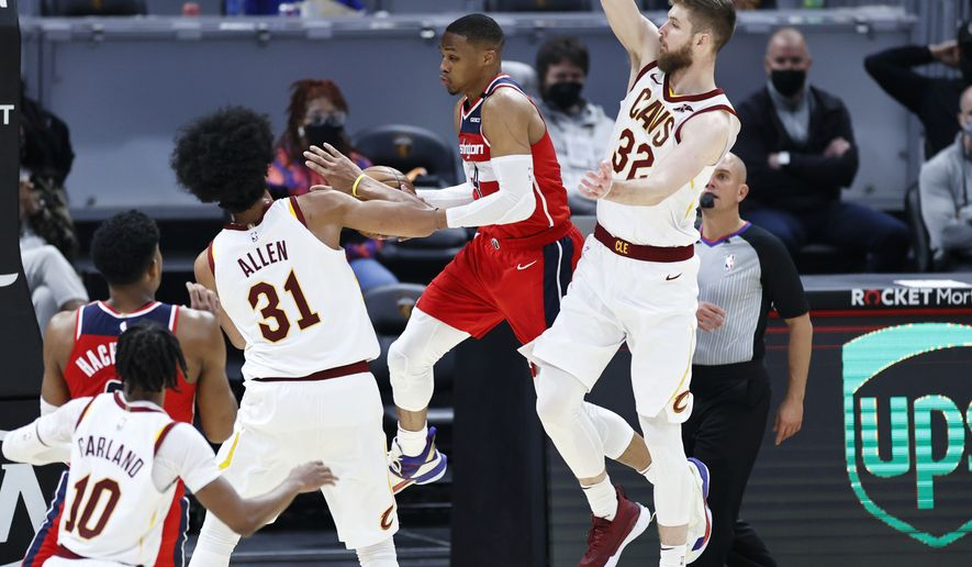 Washington Wizards' Russell Westbrook (4) looks to pass between Cleveland Cavaliers' Dean Wade (32) and Jarrett Allen (31) during the first half of an NBA basketball game, Friday, April 30, 2021, in Cleveland. (AP Photo/Ron Schwane)