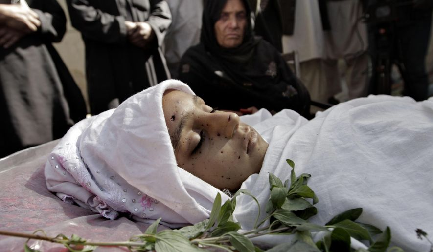 FILE - In this Oct. 27, 2013 file photo, relatives surround the body of a 10-year-old Afghan girl who was killed by a roadside bomb, apparently targeting a group of soldiers, during her funeral on the outskirts of Kabul, Afghanistan. America's longest war, the two-decade-long conflict in Afghanistan that started in the wake of the Sept. 11 terrorist attacks, killed tens of thousands of people, dogged four U.S. presidents and ultimately proved unwinnable despite its staggering cost in blood and treasure. (AP Photo/Rahmat Gul, File)