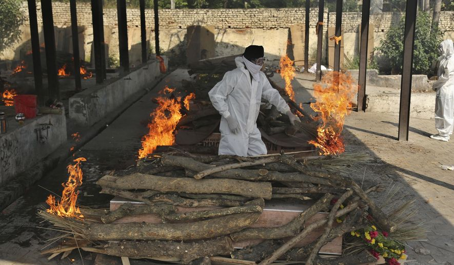 A family member performs the last rites of a COVID-19 victim at a crematorium in Jammu, in Jammu, India, Friday, April 30, 2021.  Indian scientists appealed to Prime Minister Narendra Modi to publicly release virus data that would allow them to save lives as coronavirus cases climbed again Friday, prompting the army to open its hospitals in a desperate bid to control a massive humanitarian crisis. (AP Photo/Channi Anand)