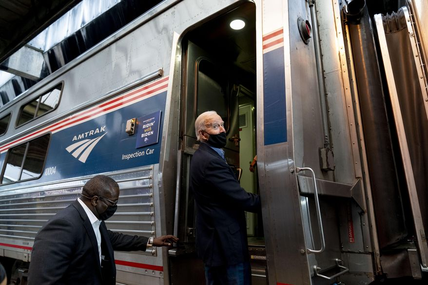 FILE - In this Sept. 30, 2020, file photo, then-Democratic presidential candidate former Vice President Joe Biden boards his train at Amtrak's Pittsburgh Train Station in Pittsburgh. President Joe Biden is set to help the nation's passenger rail system celebrate 50 years of service. (AP Photo/Andrew Harnik)