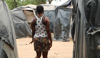 A woman who said she was trafficked from Nigeria under false pretenses to work as a sex slave in Burkina Faso's mining sites, walks through a row of tent in the Secaco mining town June 12, 2020. As part of a months-long investigation into sex trafficking and the gold mining industry, The Associated Press met with nearly 20 Nigerian women who said they had been brought to Burkina Faso under false pretenses, then forced into prostitution. (AP Photo/Sam Mednick)