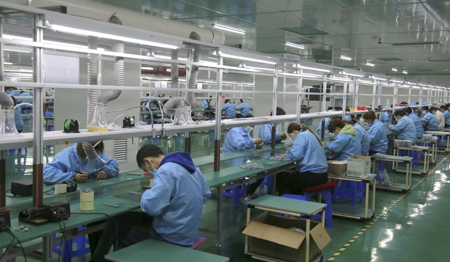 Workers put together electronic gears at a factory in Zhangye in northwestern China's Gansu Province on April 17, 2021. Two surveys show Chinese manufacturing expanded in April but growth appeared to be slowing after a rebound from the coronavirus pandemic. (Chinatopix via AP)