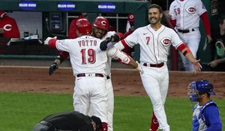 Cincinnati Reds' Joey Votto (19) is congratulated by Nick Castellanos (2) at home plate after hitting a two-run home run, his 300th career home run, in the third inning of a baseball game against the Chicago Cubs at Great American Ball Park in Cincinnati on Friday, April 30, 2021. (AP Photo/Jeff Dean)