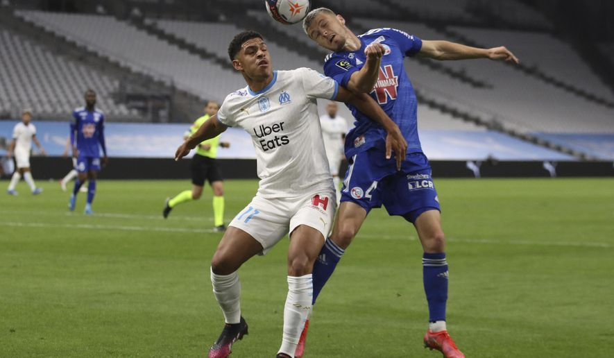Marseille's Luis Henrique, left, jumps for a header with Strasbourg's Frederic Guilbert during the French League One soccer match between Marseille and Strasbourg at the Stade Veledrome stadium in Marseille, France, Saturday, April 30, 2021. (AP Photo/Daniel Cole)
