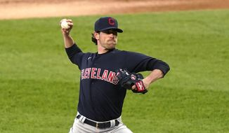 Cleveland Indians starting pitcher Shane Bieber delivers during the first inning of the team's baseball game against the Chicago White Sox on Friday, April 30, 2021, in Chicago. (AP Photo/Charles Rex Arbogast)