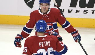 Montreal Canadiens' Nick Suzuki celebrates his goal against the Winnipeg Jets with Jeff Petry during the third period of an NHL hockey game Friday, April 30, 2021, in Montreal. (Paul Chiasson/The Canadian Press via AP)