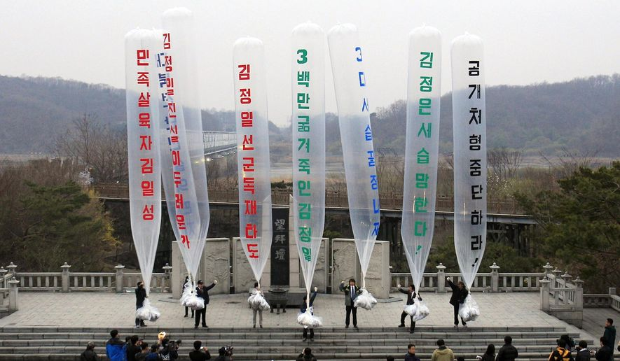 """FILE - In this April 15, 2011, file photo, Park Sang-hak, center, a refugee from the North who now runs the group Fighters for a Free North Korea from a small Seoul office, and South Korean conservative activists prepare to release balloons bearing leaflets condemning North Korean leader during an anti-North Korea rally against """"The Day of the Sun,"""" the anniversary of Kim Il Sung's birth 99 years, at the Imjingak Pavilion near the border village of Panmunjom in Paju, South Korea. Park said Friday, April 30, 2021, he launched 500,000 propaganda leaflets by balloon into North Korea this week in defiance of a contentious new law that criminalizes such actions. The balloons read """"Overthrow Kim Jong Il's dictatorship."""" (AP Photo/Lee Jin-man, file)"""