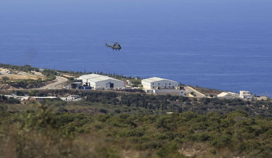 FILE - In this Oct. 14, 2020 file photo, a helicopter flies over a base of the U.N. peacekeeping force, where U.S.-mediated talks were held over a disputed maritime border between Israel and Lebanon, in the southern town of Naqoura, Lebanon. Lebanon's outgoing minister of public works said Monday, April 12, 2021, that he has signed a decree, in a unilateral move, that would increase the area claimed by Lebanon in a maritime border dispute with Israel. (AP Photo/Bilal Hussein, File)