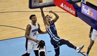 Memphis Grizzlies forward Brandon Clarke (15) shoots next to Orlando Magic center Wendell Carter Jr. (34) during the second half of an NBA basketball game Friday, April 30, 2021, in Memphis, Tenn. (AP Photo/Brandon Dill)