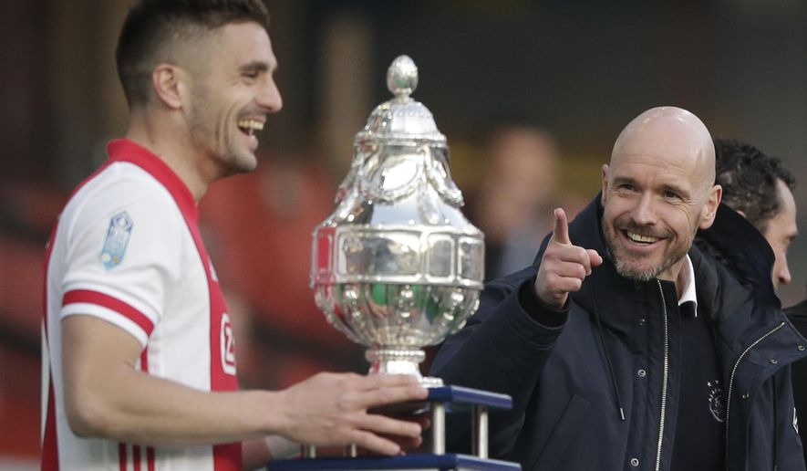 Ajax's head coach Erik ten Hag, right, gestures as captain Dusan Tadic is about to lift the trophy after winning the TOTO KNVB Cup final soccer match between Ajax and Vitesse at De Kuip stadium in Rotterdam, Netherlands, Sunday April 18, 2021. (AP Photo/Peter Dejong, Pool)