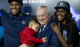 Frpm left to right, Dallas Cowboys first round draft pick linebacker Micah Parsons, his son Malcom, 2, Cowboys owner Jerry Jones and Shatra Parsons pose for photos after a news conference at Cowboys headquarters, Friday, April 30, 2021, in Frisco, Texas. (AP Photo/Brandon Wade)