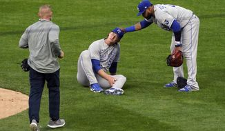 Kansas City Royals pitcher Brady Singer, center, holds his leg after a ball hit him during the second inning of the team's baseball game against the Minnesota Twins, Friday, April 30, 2021, in Minneapolis. Singer left the game. (AP Photo/Jim Mone)